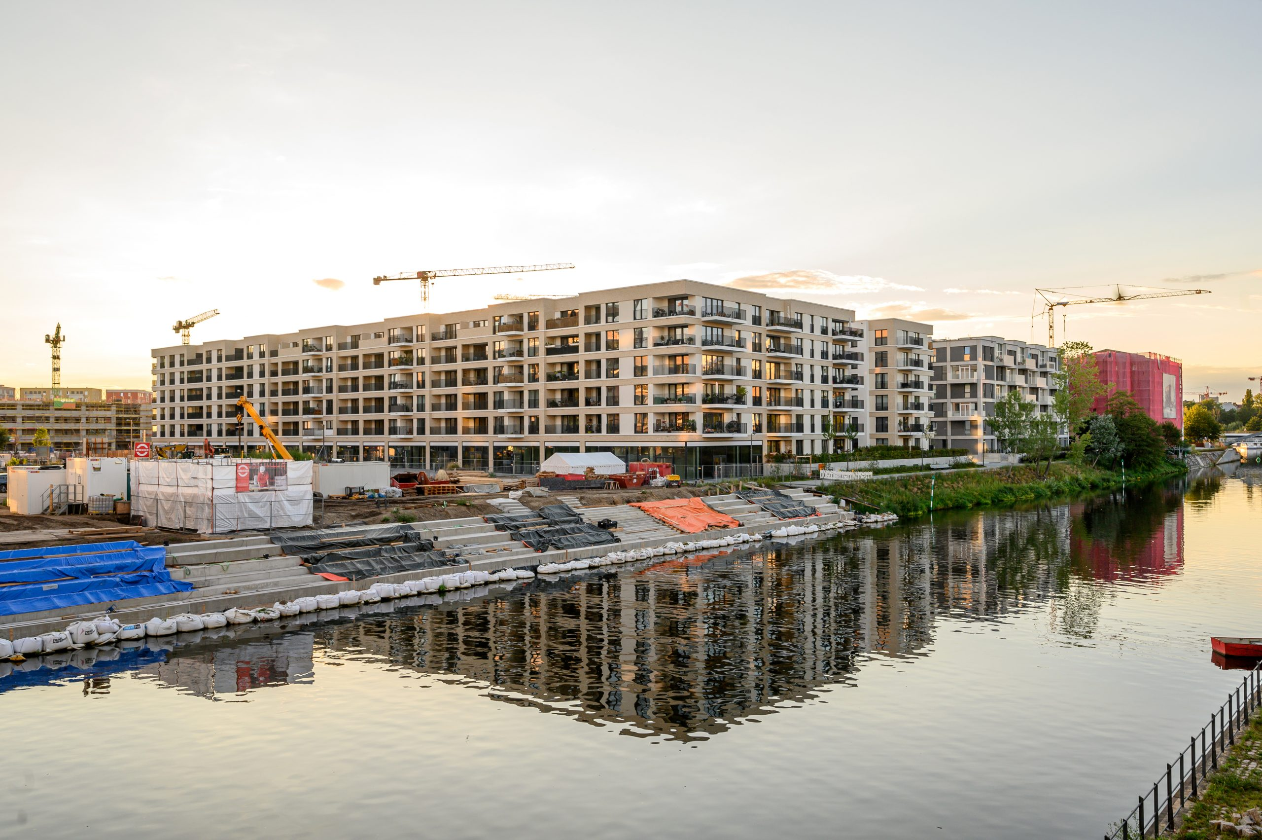 Große Freitreppe, die den Platz zum Wasser hinunter öffnet. Eine neue Verbindung vom Ostufer des Kanals zum Otto-Weidt-Platz (der Golda-Meir-Steg)